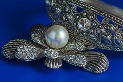 Brosch med en pärla och ett armband på en blå bakgrund Royaltyfri Foto