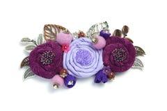 Brosch som är handgjord från ett tyg som består av blommor av lavendel- och burgundy färg på en vit bakgrund Royaltyfri Bild