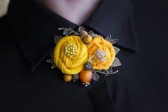 Broschen av handwork som består av två gula torkdukeblommor, fästas till en svart kvinnaskjorta Arkivfoton