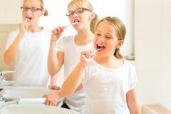 Brossage de dent de filles dans la salle de bain images libres de droits
