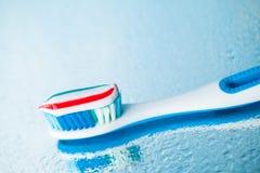 Brosse à dents avec la pâte dentifrice rouge de rayure Image stock