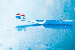 Brosse à dents avec la pâte dentifrice rouge de rayure Photos stock