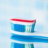 Brosse à dents bleue avec la pâte dentifrice rouge de rayure Photo libre de droits