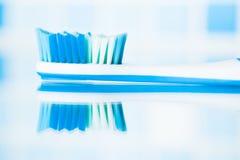 Brosse à dents bleue dans une salle de bains avec la réflexion Photos libres de droits