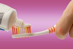 Brosse à dents et pâte dentifrice dans des mains femelles Photos libres de droits