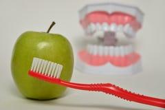 Brosse à dents et pomme verte, concept de soins dentaires Image libre de droits