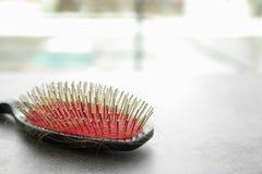 Brosse avec les cheveux perdus sur la table Images libres de droits