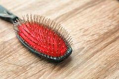 Brosse avec les cheveux perdus sur la table en bois Photo libre de droits