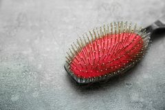 Brosse avec les cheveux perdus sur la table grise Photo libre de droits