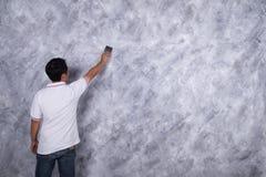 Brosse d'utilisation de travailleur pour le style concret de grenier de peinture de couleur sur le mur images libres de droits