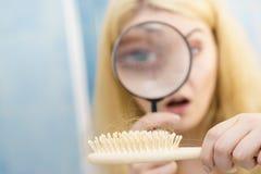 Brosse de cheveux de agrandissement de femme photographie stock