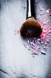 Brosse de maquillage et fards à paupières écrasés Photos stock