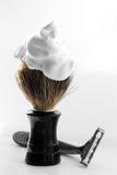 Brosse de rasage avec la mousse sur le fond blanc Image libre de droits