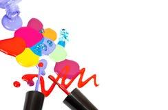 Brosse de vernis à ongles et de baisses colorées sur le fond blanc Photo stock