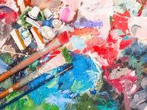 Brosse et palette lumineuse de huile-peinture pour le fond Photos stock