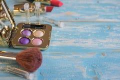 Brosse et un ensemble de cosmétiques du ` s de femmes sur une table en bois bleue image stock