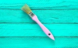 Brosse pour la peinture sur une table en bois de turquoise Tendance de minimalisme Concept d'art Vue supérieure image stock