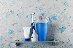 Brosses à dents électriques et manuelles en verre, pâte dentifrice, sur l'étagère photo stock