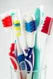 Brosses à dents colorées dans un verre d'eau Photos libres de droits