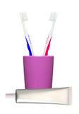 Brosses à dents dans le verre et la pâte dentifrice d'isolement sur le blanc Photographie stock