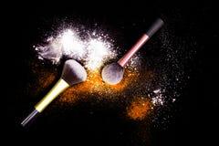 Brosses de maquillage avec la poudre colorée sur le fond noir La poussière d'étoiles d'explosion avec des couleurs lumineuses Pou Photographie stock