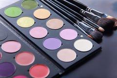 Brosses de maquillage et fards à paupières de maquillage sur le bureau Image libre de droits