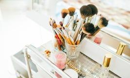 Brosses et cosmétique de maquillage sur la coiffeuse photos stock