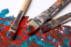 Brosses et fond utilisés de peinture avec les courses bleues et rouges Photo stock
