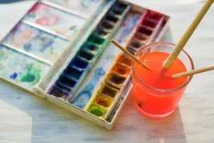 Brosses et peintures professionnelles d'aquarelle sur le rebord blanc en bois de fenêtre Photographie stock libre de droits