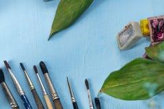 Brosses, peintures d'aquarelle, feuilles décoratives vertes et une feuille de papier sur un fond bleu Place pour le texte Vue sup photographie stock