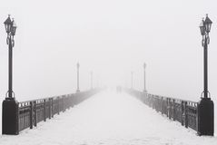 Brostadslandskap i dimmig snöig vinterdag arkivfoton