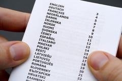 Broszura z listą języki w osob rękach Obraz Royalty Free
