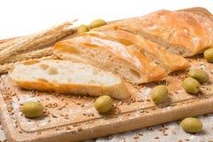 Brot auf einem Schneidebrett schnitt Zusammensetzung, Ährchen des Weizens, Oliven Lizenzfreie Stockfotografie