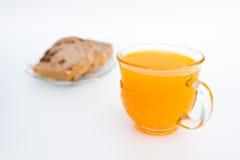 Brot auf einer weißen Platte und einem Glas Orangensaft Lokalisiert auf Weiß Stockfotos