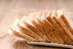 Brot in der Platte auf hölzerner Tabelle Stockfotografie