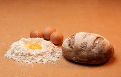 Brot, drei Eier und ein Eigelb umgeben durch Mehl Lizenzfreies Stockfoto