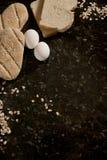 Brot, Ei, Hafer und Getreide über einer Steinabdeckung Lizenzfreies Stockbild