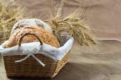 Brot in einem Weidenkorb verziert mit den Kornähren auf Holztisch Stockbild