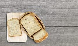 Brot in einen Korb gemacht vom Rattanschritt auf hölzerner Tabelle Stockbild