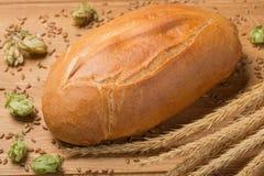 Brot liegt auf dem Brett, einer Zusammensetzung mit Weizenspitzen, Hopfen und Weizenkörnern Stockfoto