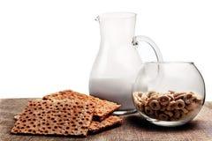 Brot, Maisringe und ein Krug Milch stockbild
