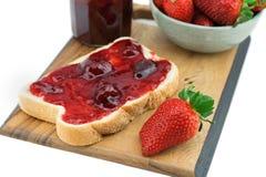 Brot mit Erdbeermarmelade auf einem hölzernen Brett stockbild