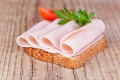 Brot mit geschnittenem Schinken, frischen Tomaten und Petersilie Stockfoto
