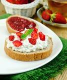 Brot mit Klumpencreme und Erdbeermarmelade Stockfoto