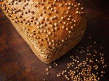 Brot mit Koriandersamen auf dunklem Holz r Lizenzfreie Stockfotografie