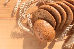 Brot mit Korn auf hölzernem Hintergrund lizenzfreie stockbilder