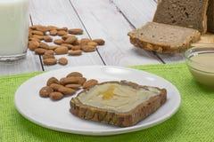 Brot mit Mandel-Butter und Honig mit Milch lizenzfreie stockfotos