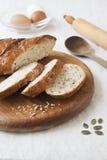 Brot mit Samen auf einem hölzernen Brett Stockbild
