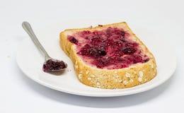 Brot mit Verbreitungsstau auf dem Teller auf weißem Isolathintergrund Stockfotografie