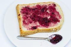 Brot mit Verbreitungsstau auf dem Teller auf weißem Isolathintergrund Lizenzfreies Stockfoto